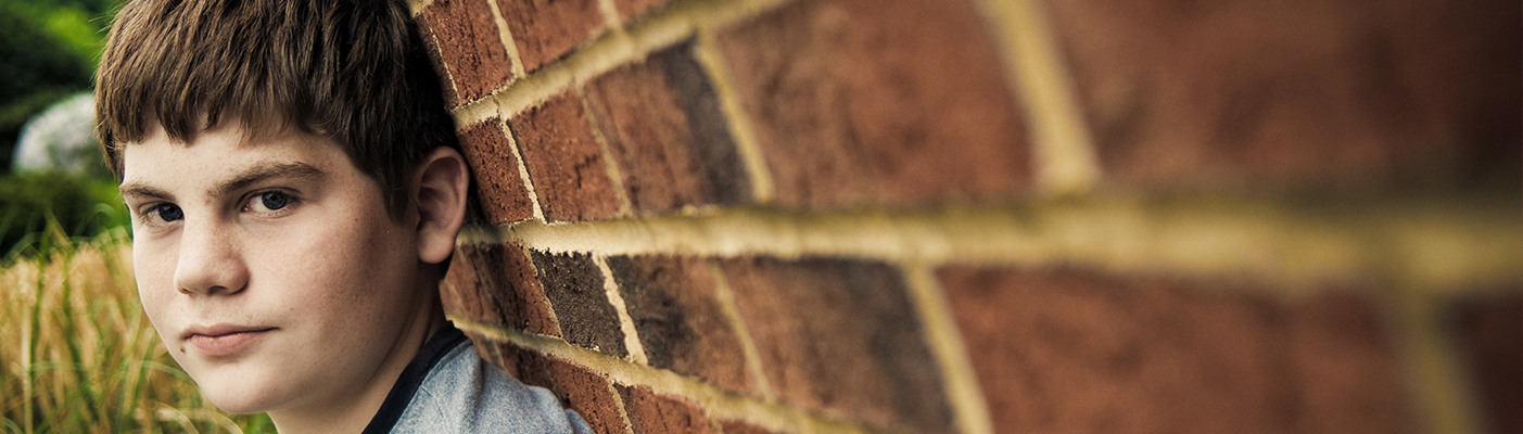 A boy is leaning against a brick wall. He is looking directly at the viewer.